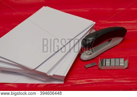 Black Office Stapler I Stationery For Paper Stitching. Stapler And Staples With Sheets Of Paper On A