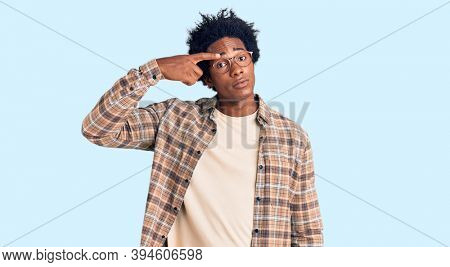 Handsome african american man with afro hair wearing casual clothes and glasses pointing unhappy to pimple on forehead, ugly infection of blackhead. acne and skin problem
