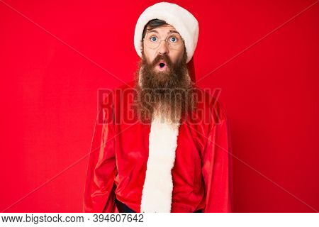 Handsome young red head man with long beard wearing santa claus costume scared and amazed with open mouth for surprise, disbelief face