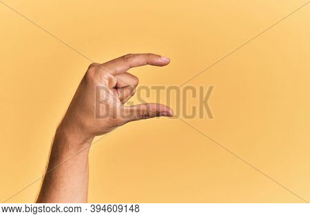 Arm and hand of caucasian man over yellow isolated background picking and taking invisible thing, holding object with fingers showing space