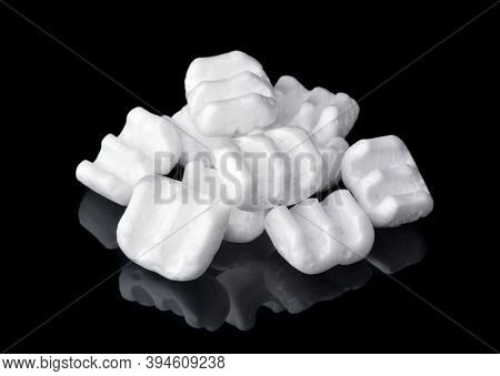 Group of m-shaped styrofoam packing chips isolated on black
