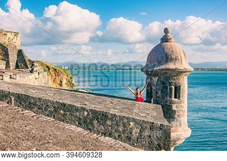San Juan Puerto Rico travel happy Asian tourist woman excited with open arms in happiness at watch tower of Castillo San Felipe del Morro summer cruise vacation.