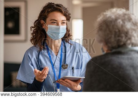 Doctor wearing safety protective mask supporting and cheering up senior patient during home visit during covid-19 pandemic. Nurse and old woman wearing facemasks during coronavirus and flu outbreak.