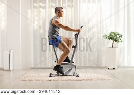 Profile shot of a fit muscular man in sportswear riding a stationary bike at home