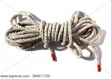Rope. A white rope bundled with both ends wrapped in red tape. Isolated on white. Room for text. Rope is used world wide for various reasons.
