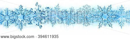 Wintry background with winter frost covered window with a pattern of ice crystals and clear snowflakes.