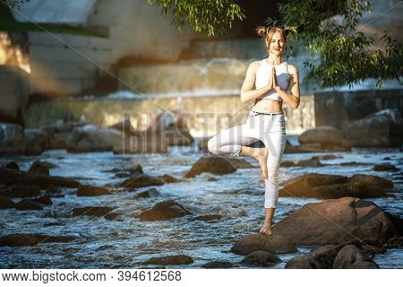 Young Slender Girl In White Practicing Yoga Outdoors. Evening Meditation And Relaxation At The River