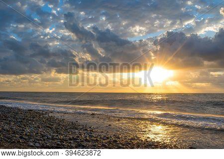 A Sunset On The Seashore. Soft Sea Ocean Waves Wash Over Golden Sand Background. Sunset, Sunrise, Su