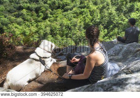 Great Barrington, Massachusetts.  September 15, 2019. A Couple And Dog Sitting On A Rocky Ledge On M
