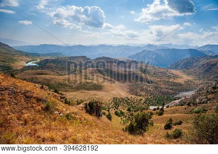 Rocky Pass With Mountain Top Views And Lakes In High Mountains. Young Men And Women Hiking Near Sary
