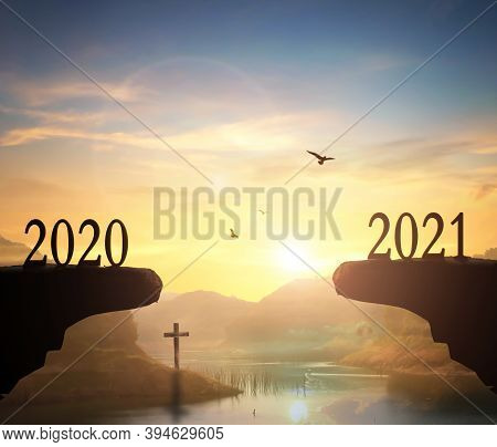 2021 Concept: Silhouette Of Year 2021 And Cross  On Mountain  With  Sunset  Background