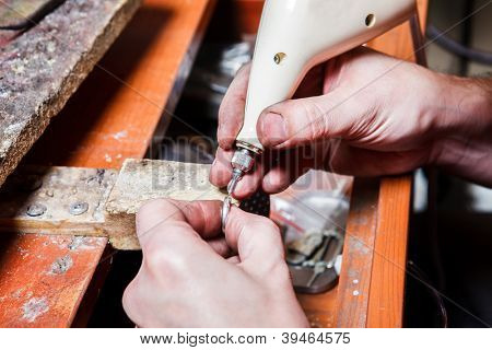 Jeweler's hands engraving on the ring