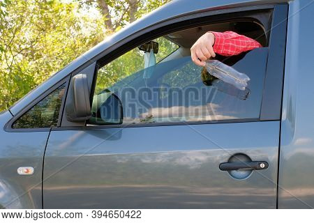 The Driver Throws A Plastic Bottle Out Of The Car Window. Rubbish On The Road. Environmental Polluti