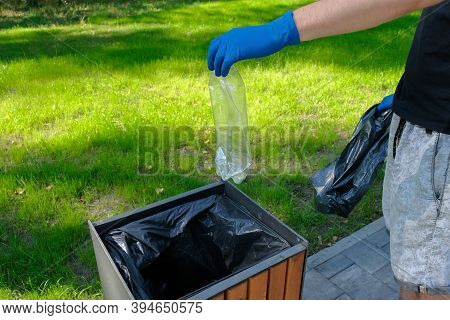 Man In Rubber Gloves Throws Plastic Trash Into The Trash Can. Environmental Protection, Ecological P
