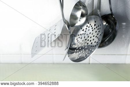 A Skimmer, Two Forks And Two Metal Ladles Hanging On The Tiled Kitchen Wall. Metal Kitchen Utensils