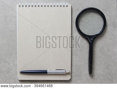 A Spring Notebook With A Sheet Of Craft Paper A5 With A Ballpoint Pen And Black Magnifying Glass On