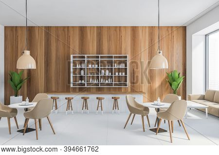 Light Brown Cafe Interior, Many Brown Chairs And White Tables, Wooden Wall With Lamps And Bar Counte