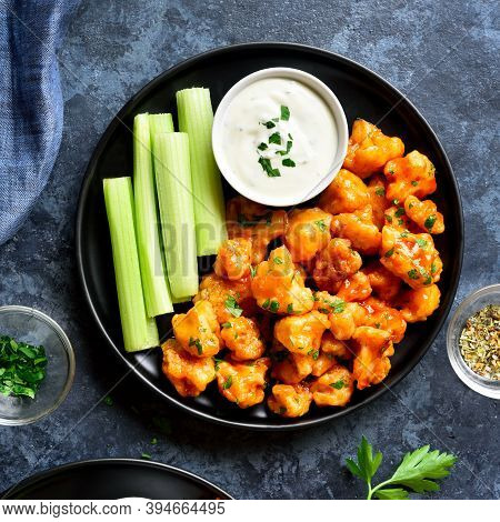 Close Up Of Cauliflower Buffalo Wings With Celery And Sauce On Plate Over Blue Stone Background. Hea