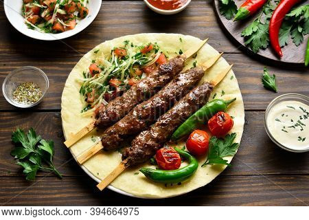 Turkish Adana Kebab With Fresh Vegetables On Flatbread Over Wooden Table.
