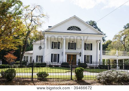 Traditional White Columned Home Behind Iron Fence