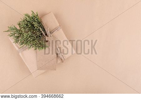 Christmas Gift Tag Mock Up With Gift Box Wrapped In Craft Recycled Paper With Rope On A Craft Paper
