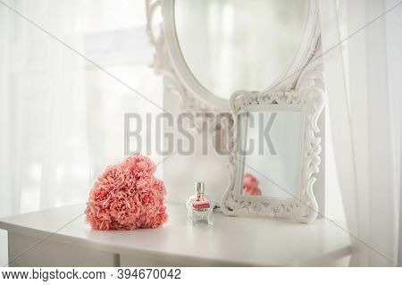 Pink Flowers On The Dressing Table In The White Bedroom. Flowers And Perfumes In A Bright Interior.
