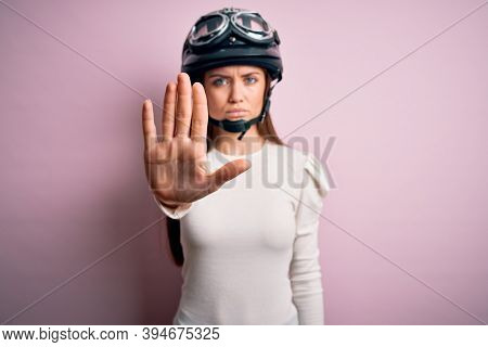 Young beautiful motorcyclist woman with blue eyes wearing moto helmet over pink background doing stop sing with palm of the hand. Warning expression with negative and serious gesture on the face.