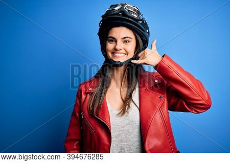 Young beautiful brunette motorcycliste woman wearing motorcycle helmet and jacket smiling doing phone gesture with hand and fingers like talking on the telephone. Communicating concepts.