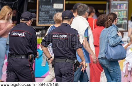 Back view of two men in police uniform walking on pavement and patrolling fairground in city