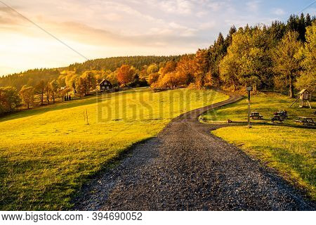 Autumn Hilly Landscape With Country Road At Sunset Time. Colorful Trees And Meadows Around Cottage U