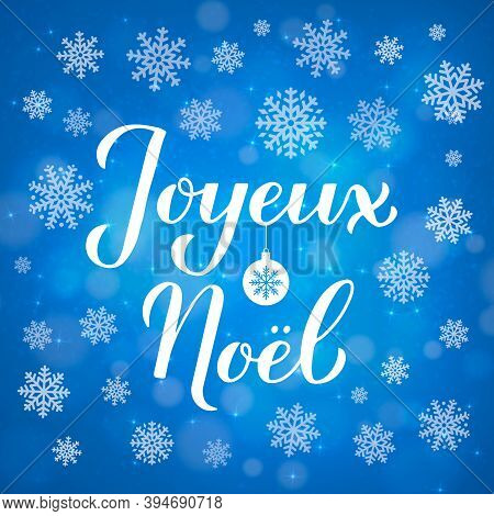 Joyeux Noel Calligraphy Hand Lettering On Blue Background With Bokeh And Snowflakes. Merry Christmas