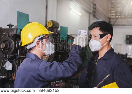 A Male Worker In A Hard Hat Is Wearing The Face Mask, Gloves, And Scanning Temperature Worker Before