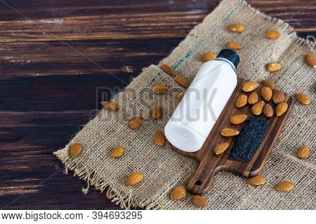 Top View Of Almond Milk With Sesame In A Plastic Bottle With Almonds Nut And Sesame Seeds On Rustic
