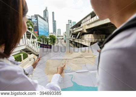 Couple Travelers Holding A Paper Map In Hands Together And Looking And Finding Destination And Stati