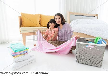 Happy Cheerful Asian Mother And Cute Daughter Sitting On The Floor In A Bedroom At Home Holding Clot