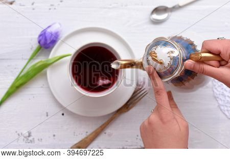 Woman Pours Hot Red Tea In A Cup On A White Wooden Table/ Fresh Blue Tulip And Cup Of Red Herbal Tea