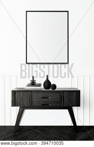 Picture frame above a wooden sideboard