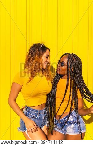 Girlfriends Lifestyle, Black Girl With Long Braids And Blonde Caucasian In Yellow Shirts And Short J