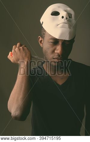 Studio Shot Of Young Black African Man Holding Mask And Pressing Scissors To His Neck In Dark Room
