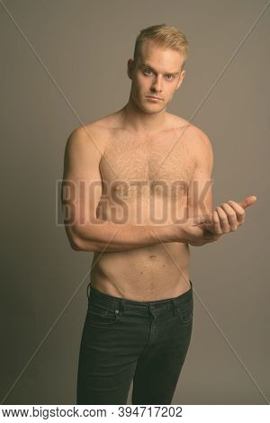 Young Handsome Man With Blond Hair Shirtless Against Gray Background