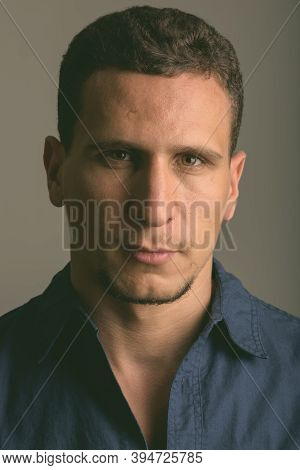 Face Of Young Muscular Persian Man Against Gray Background
