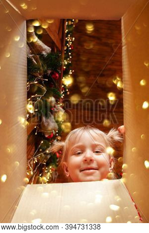 Cheerful Cute Baby Daughter Girl Opening Christmas Present. Little Child Having Xmas Fun. View From