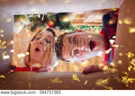 Cheerful Young Family Woman And Man Opening Christmas Present. Couple In Love Have Xmas Fun. View Fr