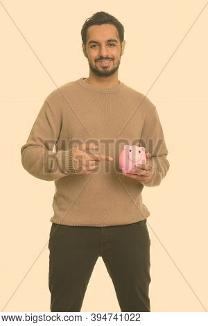 Young Happy Indian Man Holding Piggy Bank And Pointing Finger