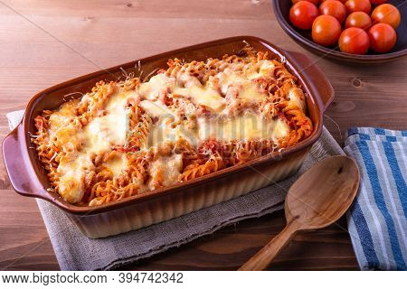 Baked Fusilli Pasta With Mozzarella And Tomato In A Pan For Baking On A Wooden Rustic Background, To