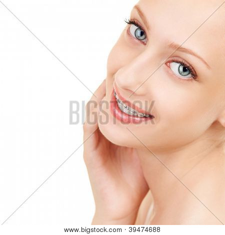 Cute girl in braces on white background