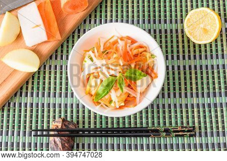 Japanese Appetizer - Salad With Radish Daikon With Apples And Carrots In A Bowl And Chopsticks On A