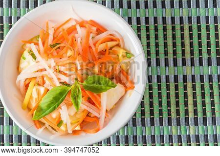 Vegetarian Appetizer - Salad With Radish Daikon With Apples And Carrots In A Bowl On A Bamboo Napkin