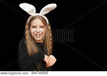 Young Girl On A Black Background With Ears Of A Hare On Her Head. She Folded Her Hands Like A Hare.