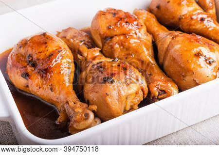 Chicken Drumstick Baked In Sweet Soy Sauce In White Ceramic Baking Dish, Close-up.